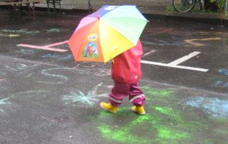 Kita-Fest: Kind unter Regenschirm